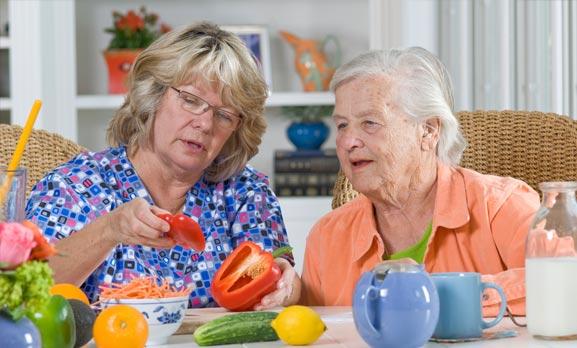 Caregiver helping senior make meal